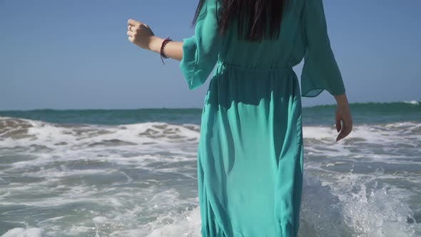 Thumbnail for Cute Woman with a Perfect Body Wearing Turquoise Dress Enjoys Sea Waves Standing in the Water