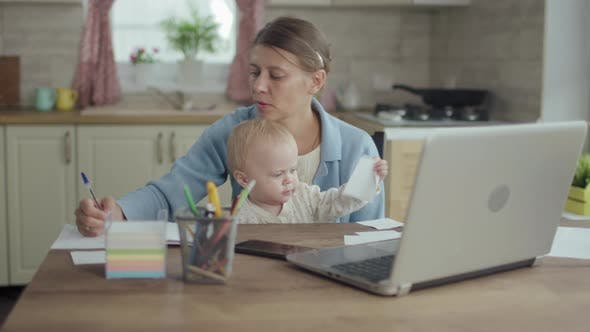 Beautiful Adult Woman Mother With Little Child Works Home