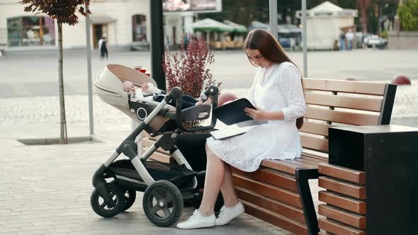 Mother Sitting on Banch with a Baby in Pram and Read Papers