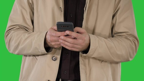 Cover Image for Man in trench coat using mobile smart phone on a Green