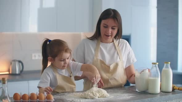 Thumbnail for The Girl and Her Mother Cook Together in the Kitchen and Mold the Dough with Their Hands