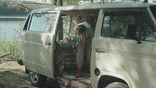Female Camper Petting Dog in Travel Trailer
