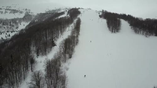Carpathian Ski Resort From a Height. Flight Over Mountains. Bird's Eye View of People Descending