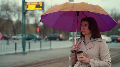 Woman Standing Under Umbrella with Coffee Cup