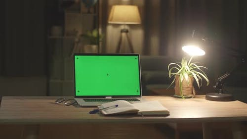 Laptop Computer Showing Green Chroma Key Screen Stands On A Desk In The Living Room