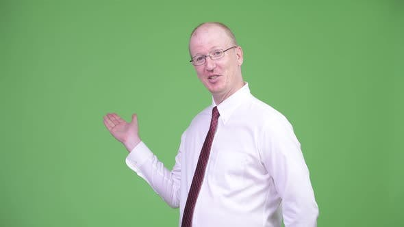 Thumbnail for Mature Bald Businessman Presenting Something