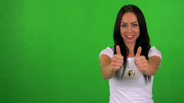 Cover Image for Young Pretty Woman Shows Thumbs Up on Agreement - Green Screen - Studio