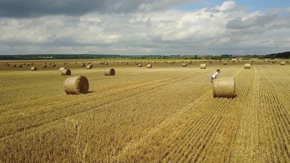 Child Boy In The Field. Child boy in the field against straw bales