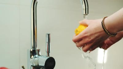 Woman's Hands Wash a Lemon Under the Tap with Water