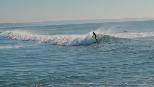 Surfer riding a big blue wave of the Atlantic Ocean on a beautiful sunny day