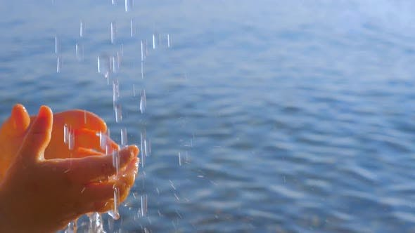 Thumbnail for Kids Hands Reaching Out the Drops of the Water. Water Pouring From the Top on Little Childs Hands