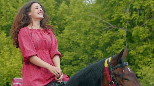Thumbnail for Young Smiling Woman with Braces in Pink Dress Riding a Horse