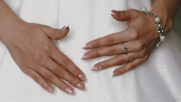 Bride in Shining Dress Shows Hands with Rings and Bracelet