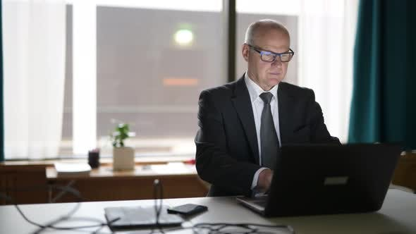 Cover Image for Happy Senior Businessman Using Phone And Laptop At Work