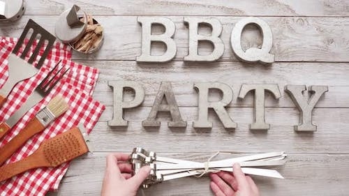 BBQ Party sign with BBQ cooking tools on a wood background.