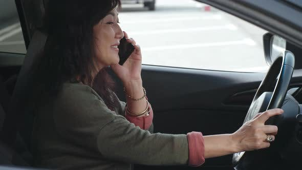 Thumbnail for Mid-Aged Asian Woman Chatting on Phone in Car