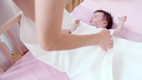 Thumbnail for Mother swaddling baby girl
