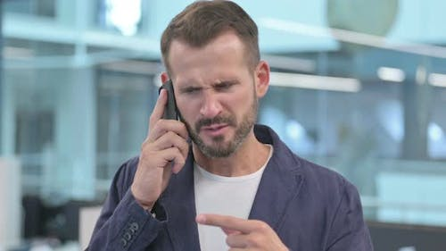 Angry Middle Aged Businessman Talking on Smartphone