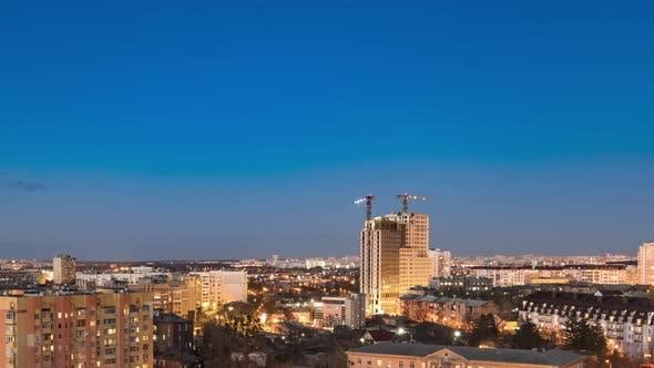 Nachtstadtbild und große Turmkrane bauen mehrstöckige Gebäude