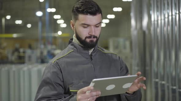 Thumbnail for Portrait of Concentrated Bearded Caucasian Man Standing at Production Site and Using Tablet. Modern