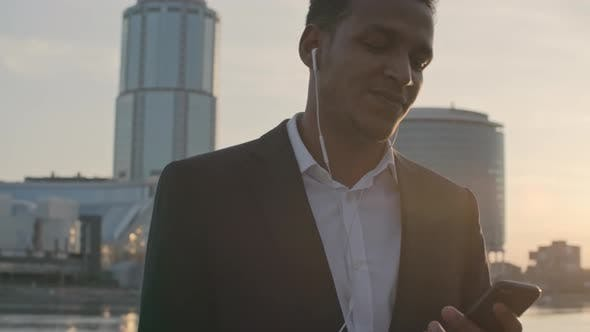 Thumbnail for Businessman Listening to Music on Smartphone
