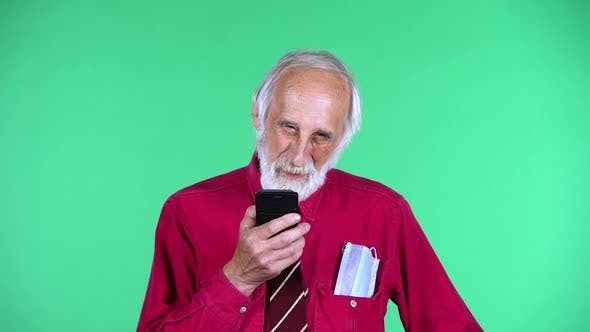 Portrait of Happy Old Aged Man 70s Talking for Mobile Phone, Isolated Over Green Background.