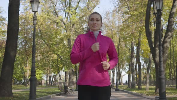 Thumbnail for Young Caucasian Woman in Sportswear and Headphones Running in the Autumn Park