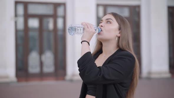 Thumbnail for Schöne Brünette Junge Frau trinkt Wasser aus Flasche in der Stadt