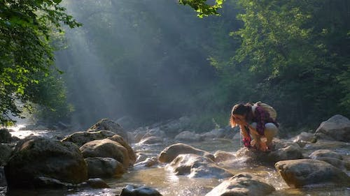 Woman Traveler Drinks Clean Water From River or Spring in Summer Forest