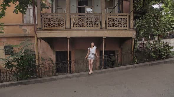 Cover Image for The Girl Admires the View of Tbilisi Streets, Georgia. Typical Architecture of Old Part of City