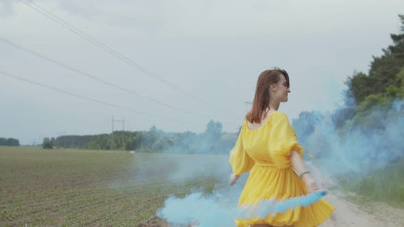 Thumbnail for Smiling Woman Whirling in Color Smoke Among Field