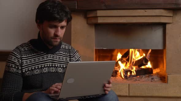 Woman Using a Digital Laptop Sits By the Fireplace