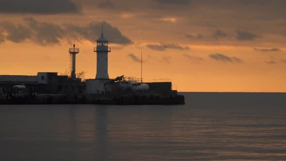 Thumbnail for Lighthouse At the Port Against the Sky At Sunset