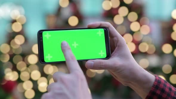 Thumbnail for Hands Of Young Man Using Phone Against Illuminated Christmas Trees Outdoors
