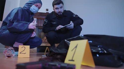 Porträt von ernsthaften kaukasischen Polizisten diskutieren Beweise am Tatort. Forensische