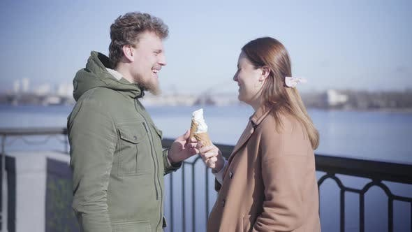 Thumbnail for Positive Caucasian Boyfriend and Girlfriend Holding Ice Cream and Chatting Outdoors. Happy Young