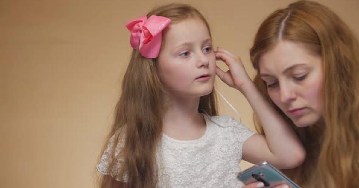Little Girl Puts On Earphone Portrait