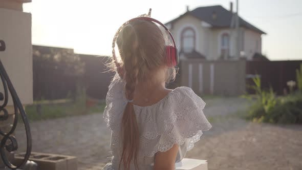 Cover Image for Back View of a Pretty Cute Little Girl in Headphones Reading the Book Sitting on the Porch Waving