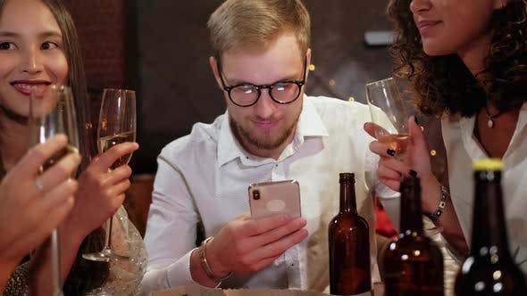 Thumbnail for Friends in a Pub Celebrate and Have Fun, One Guy Is Looking at a Smartphone, and Not Talking