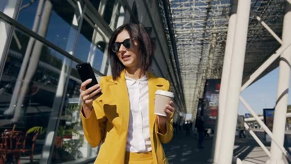 young professional businesswoman in a classic suit uses a smartphone and drink coffee