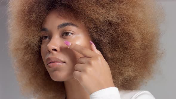 Mixed Race Black Woman with Big Afro Hair in Studio Put a Cream Smudge
