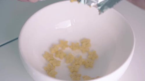 Crunchy Cereals in Star Shape Falls Down From Packet