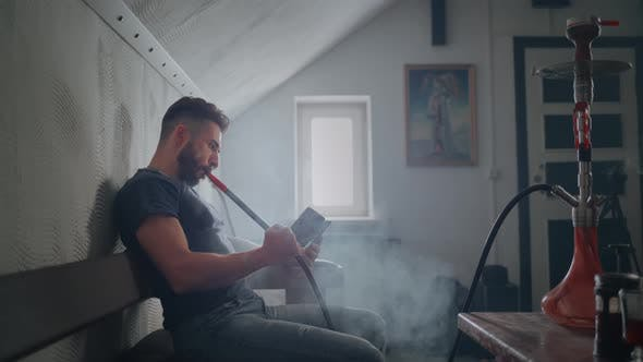Thumbnail for The Guy Smokes a Hookah Indoors and Exhales Smoke