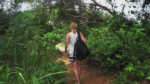 Thumbnail for traveler girl with a backpack walking along a trail on a tropical island, watching forest