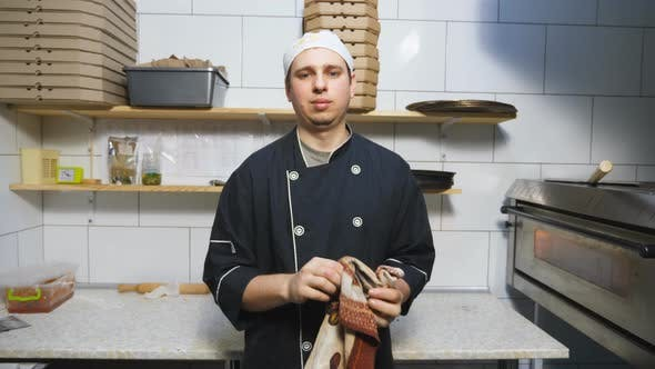 Portait of Young Cook in Uniform Standing at Kitchen Restaurant and Wiping His Hands with a Towel