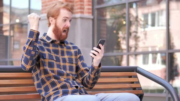 Cover Image for Man Celebrating Win on Smartphone, Sitting Outdoor on Bench
