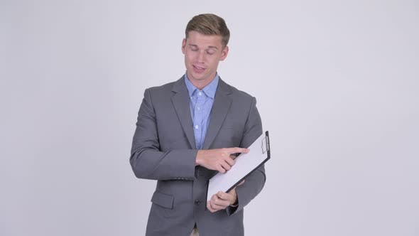 Thumbnail for Happy Young Businessman Showing Clipboard and Giving Thumbs Up