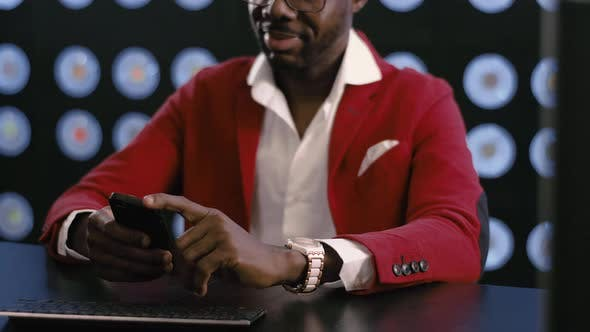 Thumbnail for Cute african-american businessman in red suit uses smartphone in dark room.
