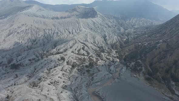 Thumbnail for Aerial view flying over volcanic sand towards an active volcano
