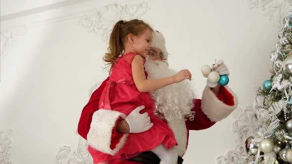Thumbnail for Weihnachtsmann Helping Little Girl zum Aufhängen von Kugeln auf dem Weihnachtsbaum